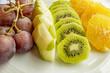 bunch of grapes, sliced kiwi, apple and orange fruits in white plate