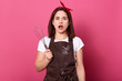 canvas print picture - Image of astonished good looking female standing isolated over pink background in studio, opening her eyes and mouth widely, looking directly at camera, holding whisk in one hand. Cook concept.