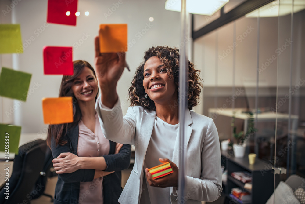 Fototapeta Creative businesswoman writing on sticky notes on a glass wall, female colleague looking.