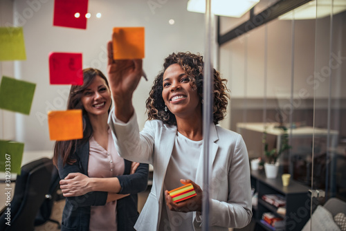 Fotografía Creative businesswoman writing on sticky notes on a glass wall, female colleague looking