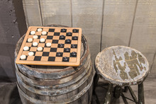 Old Fashioned Game Of Checkers. Checkerboard Game With Checkers On An Old Wooden Keg Barrel With Old Wood Stool.