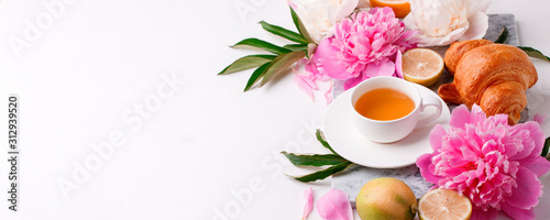 Peonies and cup of tea on white background. Spring flowers. Spring breakfast ...