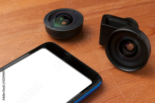 Blank screen smartphone on wooden table with some add on lenses Canvas Print