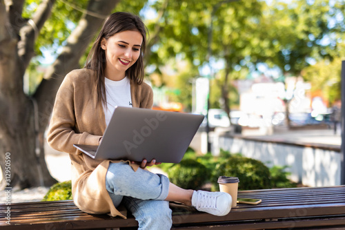 Young beautiful business woman working on a laptop sitting on the bench in the s Canvas Print