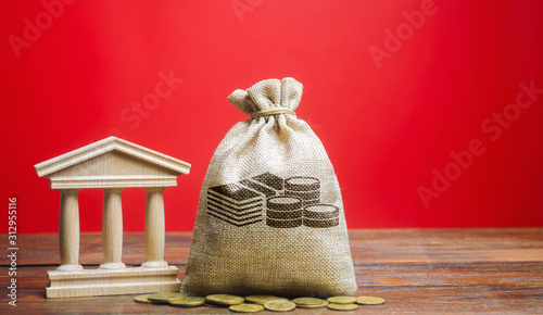 Fototapeta Money bag and government building. Business and finance concept. Deposit, loan and investment in to the bank. Credit. Help from the state. Subsidies and Benefits. Budget. Copy space obraz