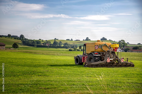 Photo Application of manure on arable farmland with the heavy tractor who works at the
