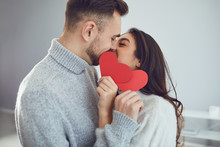 Valentine's Day. Loving Couple With Hearts In Hand Kisses In The Room