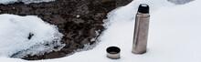 Vacuum Flask On Snow Near Flow...