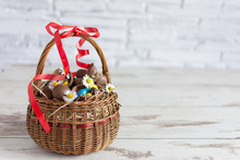 Chocolate Easter Eggs In Basket On Wooden Background. Copy Space.