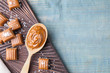 Salted caramel on blue wooden table, top view. Space for text