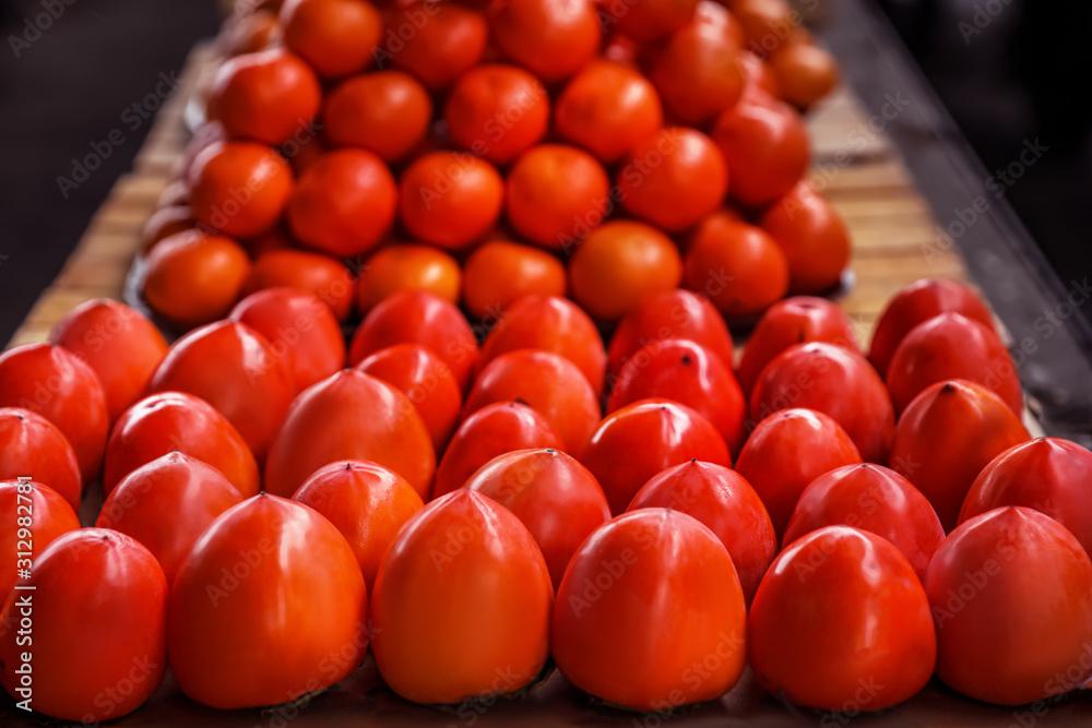 Fototapeta Fresh ripe persimmon fruit on counter at wholesale market