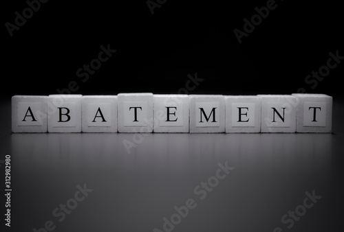 The word ABATEMENT written on wooden cubes isolated on a black background Wallpaper Mural