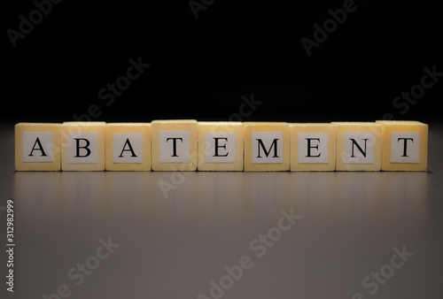 Photo The word ABATEMENT written on wooden cubes isolated on a black background