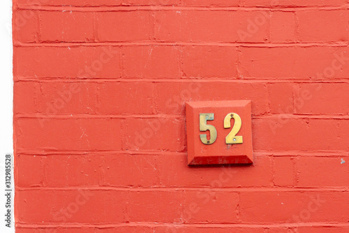Tela  House number 52 on an orange wall