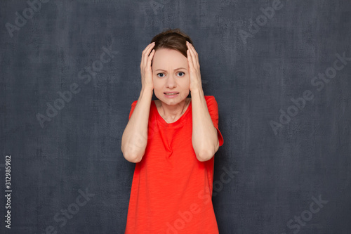 Portrait of upset disappointed young woman raising hands to head Tablou Canvas