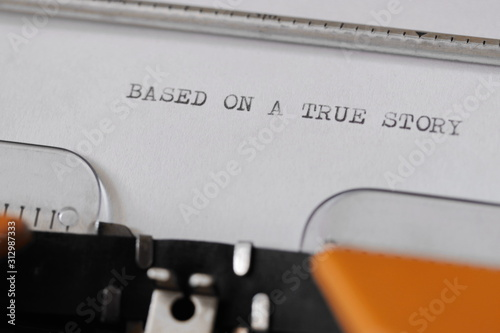 Photo Close up footage of ˝BASED ON A TRUE STORY˝ written on a paper, on an old typewriter with capital letters