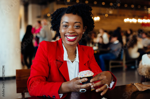 Fotografía  Portrait of a smiling, happy young woman sitting in a cafe holding a sprinkles c