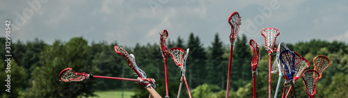Fotografía lacrosse raised lacrosse sticks against the sky