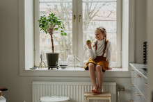 Smiling Girl Sitting On Windowsill