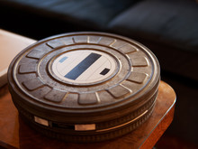 Close-up Of Old Metal Movie Film Reel Canisters On A Wooden Table
