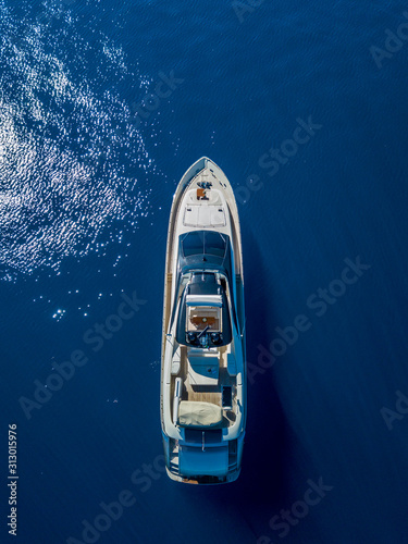 Aerial vertical shot of a yacht sailing on the sea