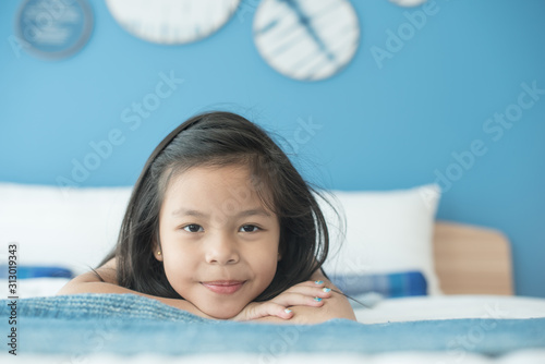 Obraz adorable little child girl sleeping in the bed. a nice child girl enjoys sunny morning. good morning at home. child girl wakes up from sleep. health and beauty concept - fototapety do salonu