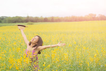 Asia Woman With A Hat In Her Hand Walks In A Field With Field Flowers And Smiles Sincerely, Happy Enjoying Summer In Yellow Field At Sunset. Smiling With Arms Raised Up.  Concept Of Freedom.