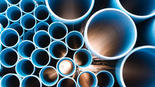 Blue Plastic Pipes Used In Construction Site.Blue PVC Water Pipe In Storage.Packaged Blue Plastic Water Pipes At Warehouse.