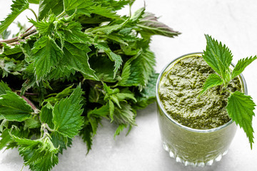 Detox juice or green smoothie with leaves of nettle blended in a glass