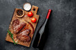 two grilled beef steaks in the form of a heart with spices and a bottle of wine for dinner for Valentine's day on a stone background with copy space for your text