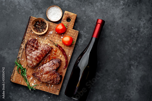 Fotografia two grilled beef steaks in the form of a heart with spices and a bottle of wine