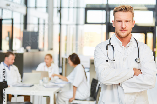 Young man as a doctor with crossed arms #313057568