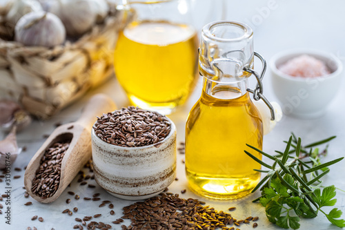 Fototapeta Flaxseed oil in a bottle and ceramic bowl with brown flax seeds and wooden spoon on a white background. obraz