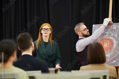 Fototapeta Woman and man preparing for the presentation they are going to present paintings to business people obraz na płótnie