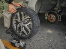 Man Changing Spare Wheel On A Roadside. Patch And Plug Hole In Tire.