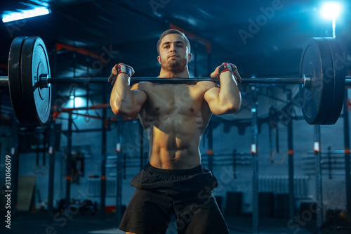 Obraz Caucasian man practicing in weightlifting in gym. Caucasian male sportive model training with barbell, looks confident and strong. Body building, healthy lifestyle, movement, activity, action concept. - fototapety do salonu