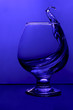 canvas print picture - Cognac pouring into a glass in blue