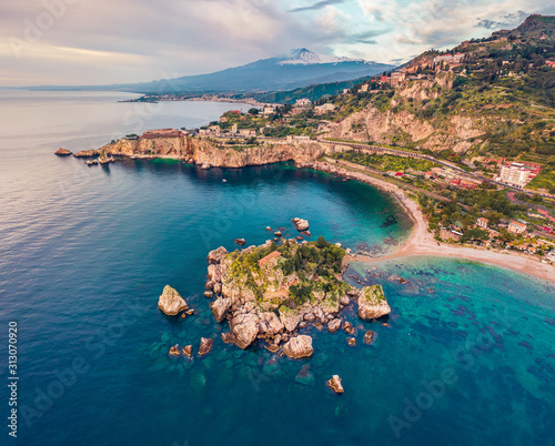 View from flying drone. Breathtaking morning view of Bella island and Etna volcano on background. Nice spring seascape of Mediterranean sea. Aerial view of Taormina town, Sicily, Itale, Europe. Fototapete