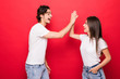 Leinwanddruck Bild - Photo of cheerful cute nice positive pretty boyfriend students girlfriend clapping their palms giving high five smiling toothily laughing in white t-shirts isolated red color background