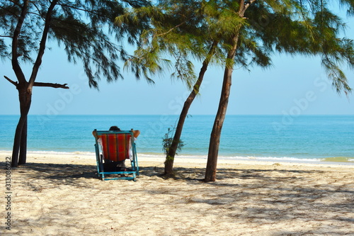 Photo relax on sun lounger on beach under the palm trees