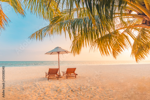 Obraz Beautiful tropical sunset scenery, two sun beds, loungers, umbrella under palm tree. White sand, sea view with horizon, colorful twilight sky, calmness and relaxation. Inspirational beach resort hotel - fototapety do salonu