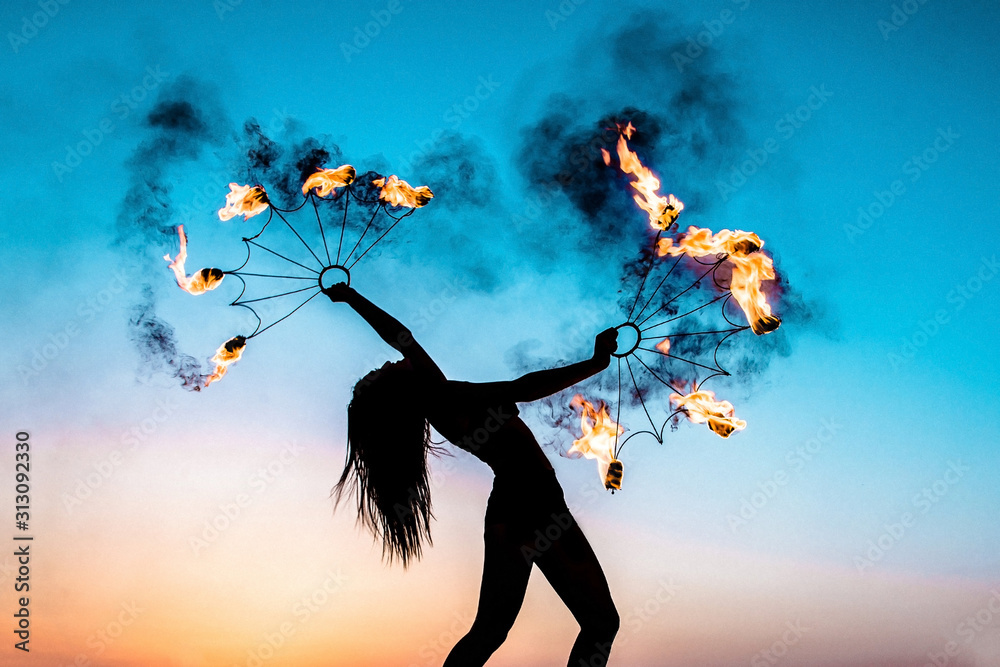 Fototapeta Fire show at sunset. Silhouette of a girl with burning torches