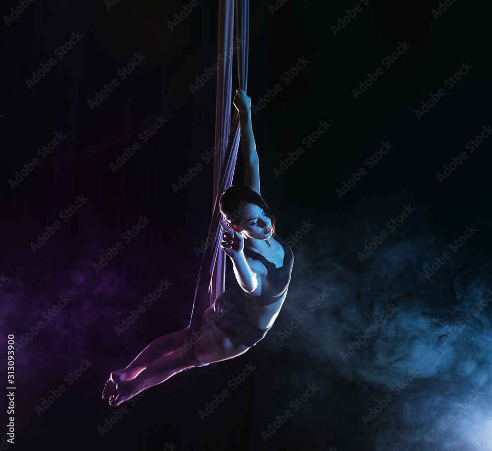Young woman performing acrobatic element on aerial silk against dark background. Space for text