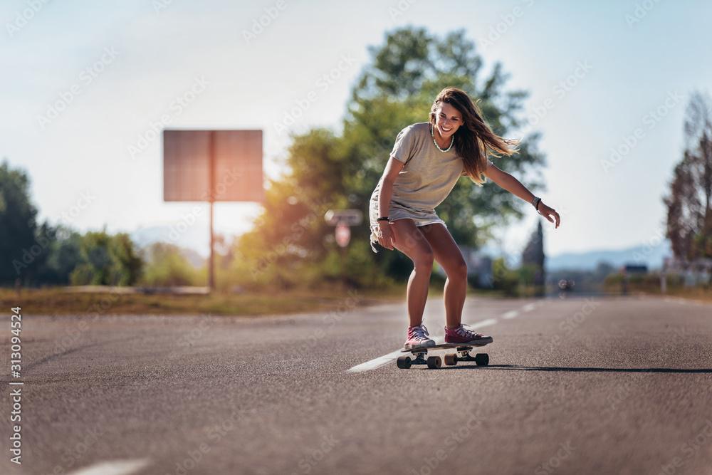 Fototapeta Sporty woman riding on the skateboard on the road. Longboarding, female.