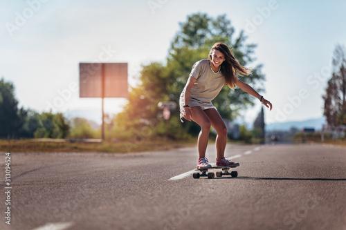 Obraz Sporty woman riding on the skateboard on the road. Longboarding, female. - fototapety do salonu