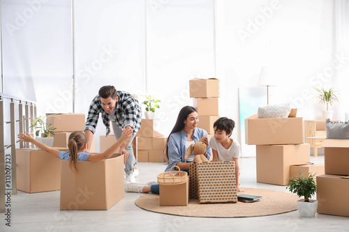 Happy family having fun while unpacking moving boxes at their new home Canvas Print