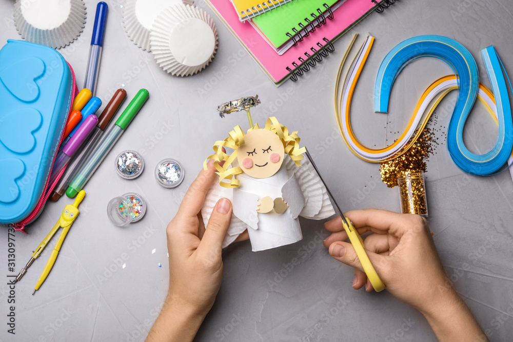 Fototapeta Woman making toy angel from toilet paper hub at grey table, top view