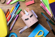 Toy Unicorn Made Of Toilet Paper Roll Among Stationery  On Wooden Table, Flat Lay