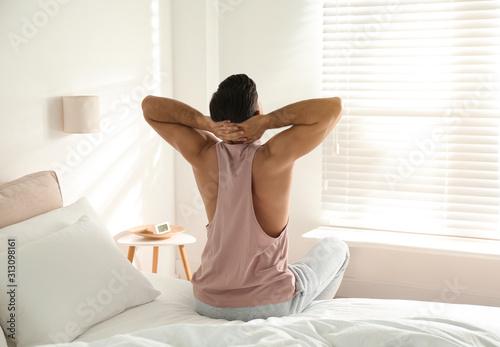 Obraz Man awakening on bed at home. Lazy morning - fototapety do salonu