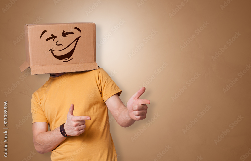 Fototapeta Young boy standing and gesturing with a cardboard box on his head